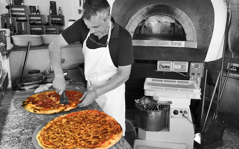 Foto del pizzero con el horno napolitano de piedra